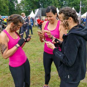 Drei Frauen am Handy vor dem Start